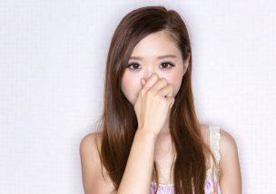 汗の臭いに鼻をつまむ女性。